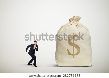 businessman in formal wear showing silent sign and sneaking to the big bag of money over light grey background