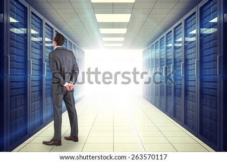 Businessman in grey suit looking against digitally generated server room with towers