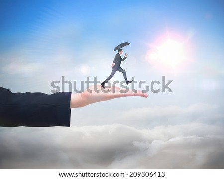 Businessman jumping holding an umbrella against blue sky with sunshine and clouds