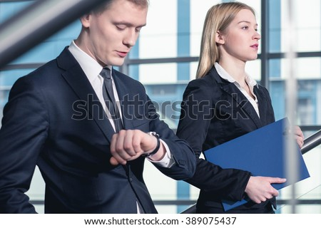 Businessman looking on wristwatch and businesswoman holding a blue folder