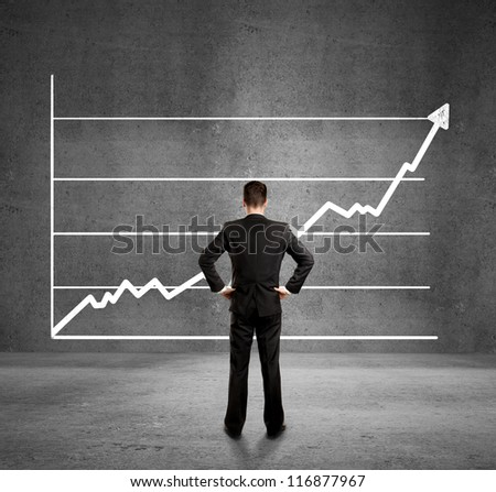 businessman looks at growth chart