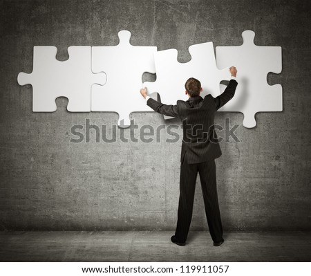 Businessman making a puzzle on the wall