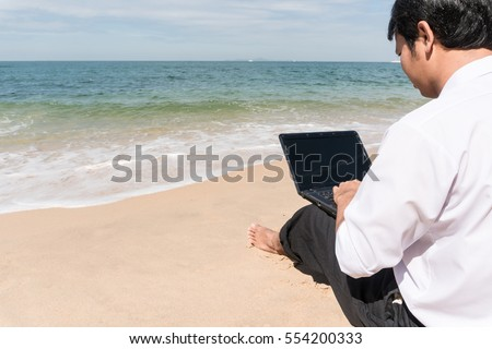 Businessman office Dress relax sit on the beach, copy space on Left side, Holiday vacation time concept.