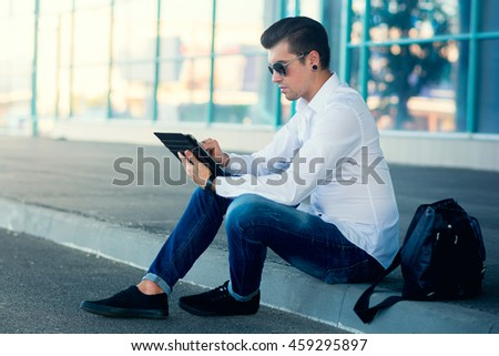 Businessman outside building with electronic tablet sitting on side of road near business centre