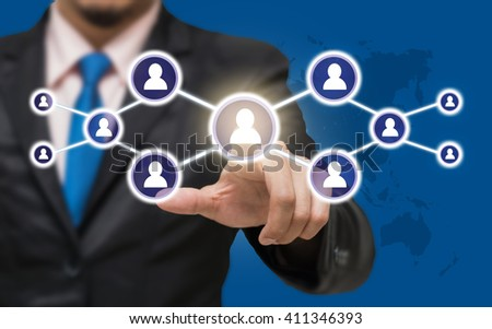 Businessman pointing or touching the Social media symbol on blue color background with world map,Elements of this image furnished by NASA, Business network concept