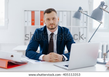 Businessman portrait, at office working at his laptop