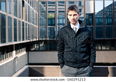 Businessman portrait with modern building as background.