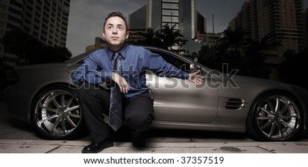 Businessman posing by a luxury sports car