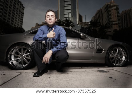 Businessman posing by a luxury sports car and gesturing with a thumb-up