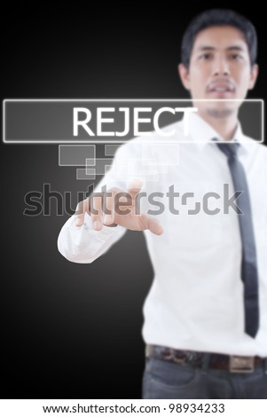 Businessman pushing Reject word on a touch screen interface.