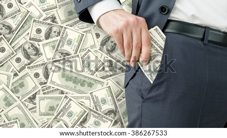 Businessman putting one hundred dollar banknotes into the pocket. Only trousers seen. Dollars at background. Concept of winning a fortune.