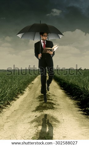 Businessman reading a book under umbrella shot outdoor