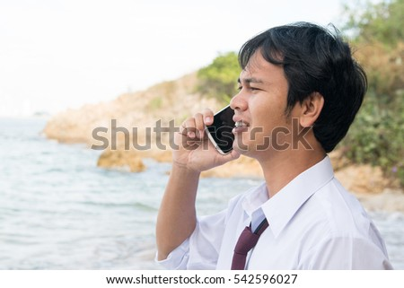 Businessman relax office Dress standing talking mobile phone on the beach, Holiday vacation time concept.