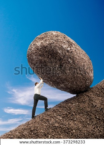 Businessman rolling up giant boulder on slope over blue sky