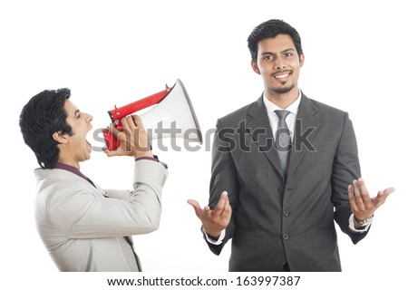 Businessman shouting at his colleague with a megaphone