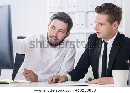 Businessman showing his colleague details on his current project. Concept of department collaboration within one company