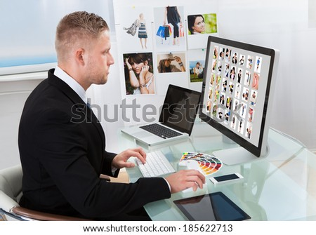 Businessman sitting at his desk in front of a large screen monitor editing photographs
