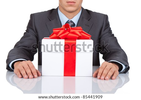 Businessman sitting at the desk with gift box isolated over white background, series photo