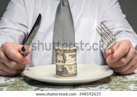 Businessman sitting behind a table with fork and knife ready to eat a wad of dollars served on plate - business concept