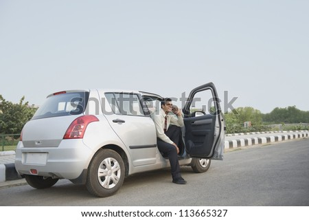 Businessman sitting in the car and talking on a mobile phone