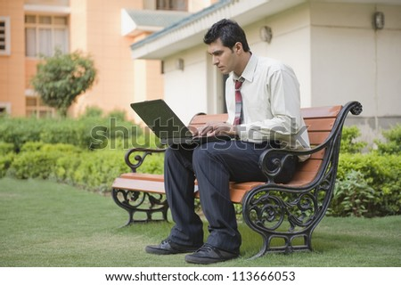 Businessman sitting on the bench and using a laptop