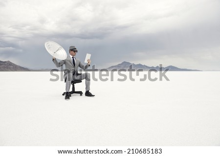 Businessman sitting outdoors in dramatic desert landscape holding satellite communication receiver and digital tablet