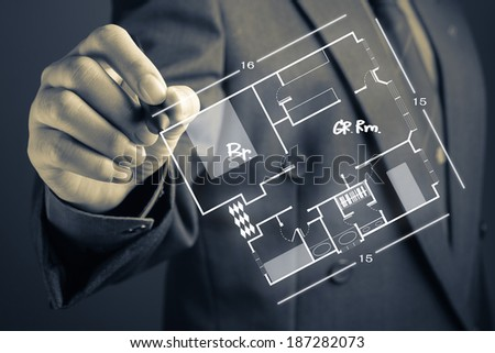 Businessman sketching house plan on screen