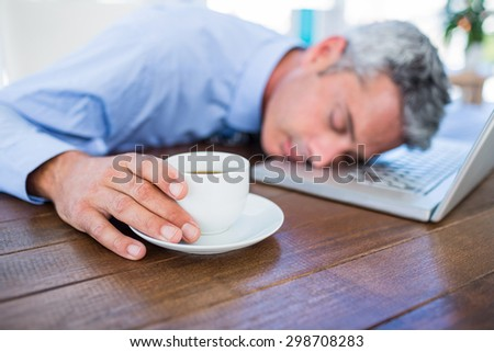Businessman sleeping on laptop computer and touching coffee cup in office