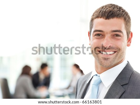 Businessman smiling at the camera while his team is working in the background