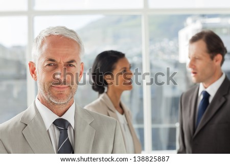 Businessman standing in front of colleagues speaking together in their office