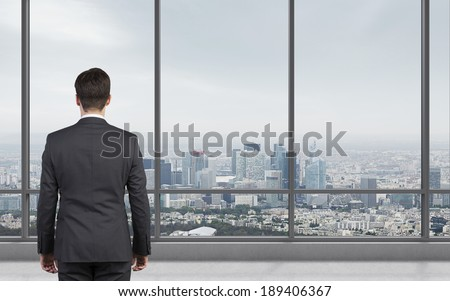 Businessman standing in front of window. City view.