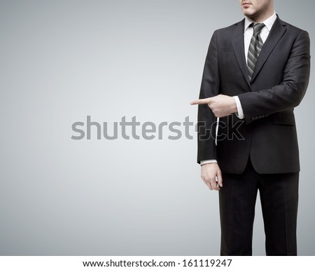 businessman standing in suit and showing  finger to something