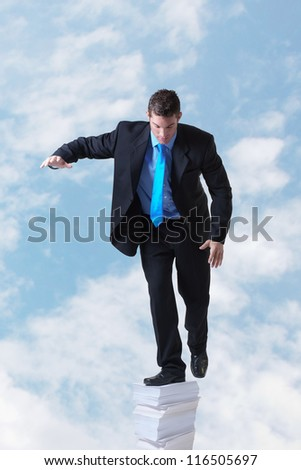 businessman standing on a large pile of paper going right up into the sky