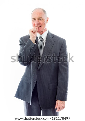Businessman standing with finger in mouth