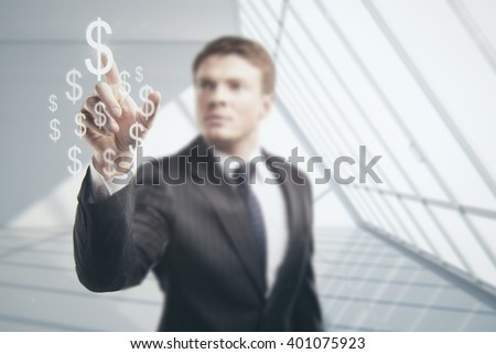 Businessman touching soaring dollar signs on blurry white interior background