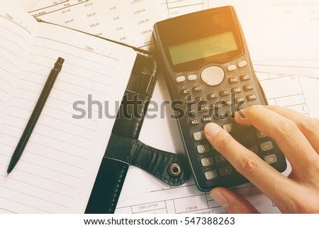 Businessman using calculator counting making notes about cost at home office.