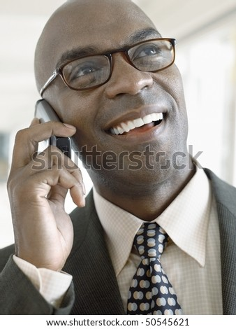 Businessman using mobile phone, indoors, (close-up)