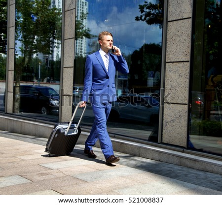 Businessman walking outdoors, pulling suitcase behind him