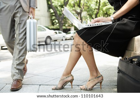 Using her laptop computer while sitting down outdoors stock photo