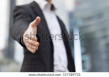 Businessman with an open hand ready to seal a deal with buildings background