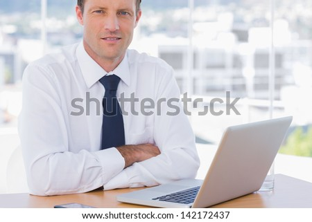 Businessman with arms folded on his desk in his office