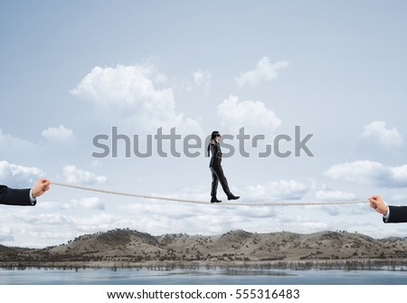 Businessman with blindfolder on eyes walking on rope over gap