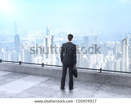 businessman with briefcase standing on roof and looking at city