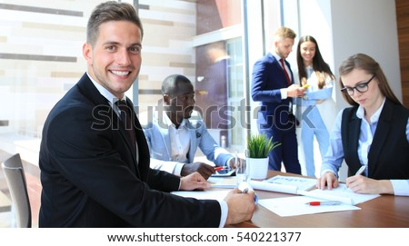 Businessman with colleagues in the background in office