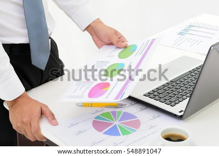 businessman working in office reading documents at office desk and using laptop computer. Business concept.