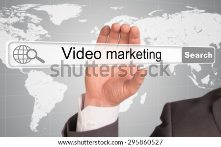 Businessmans hand holding browser with words video marketing on abstract background