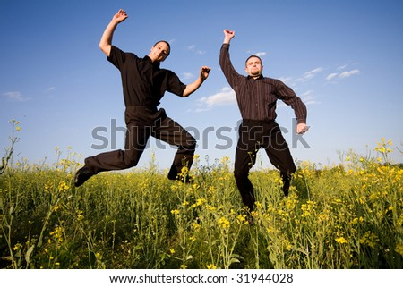 businessmans jumping in rapeseed