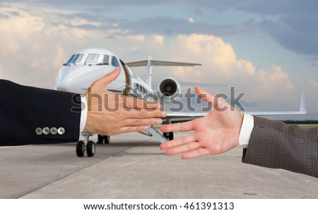 Businessmen about to shake hands in front of corporate jet. Focus on hands