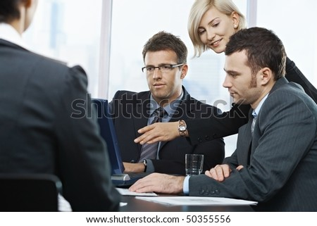 Businessmen looking at laptop, businesswoman pointing at screen in office, at meeting table,