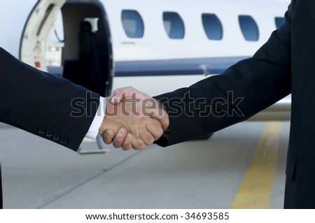 Businessmen shaking hands in front of corporate jet.  Focus on hands
